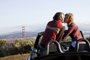 """USA, California, San Francisco, young couple sitting in convertible car and kissing, Golden Gate Bridge in background"""