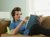 """USA, Utah, Provo, young man lying down on sofa and reading book"""