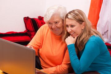 seniorin und junge frau sitzen an laptop und haben spass