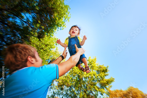 happy daddy is throwing  baby in a greenl summer park