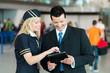 Freundliche Stewardess und Business-Mann analysieren etwas am Ta