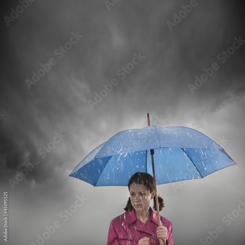 """USA, Utah, Orem, woman with umbrella standing in rain"""