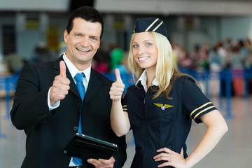 Business-Mann und Stewardess zeigen Daumen hoch