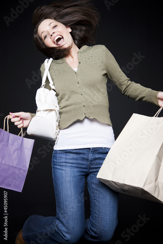 Studio portrait of young woman jumping with shopping bags