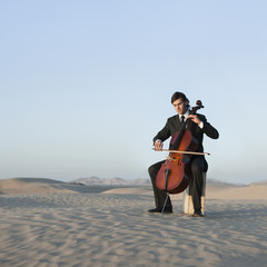 """USA, Utah, Little Sahara, young man with cello in desert"""