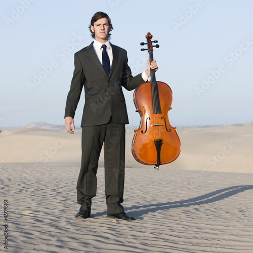 """USA, Utah, Little Sahara, portrait of young man with cello in desert"""