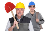 Experienced tradesman standing in front of his apprentice poster
