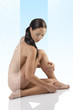 naked brunette sitting on a floor looks down