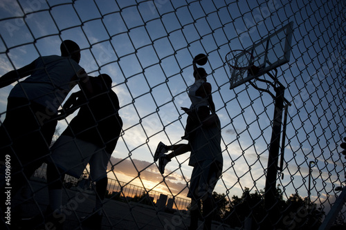 """USA, Utah, Salt Lake City, four young men playing street basketball, low angle view"""