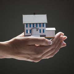 Toy house in young woman's hands