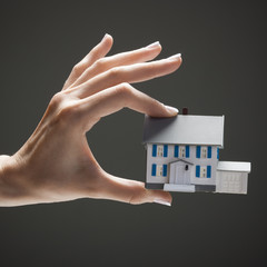 Young woman's hand holding toy house