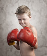 Non Aggressive child wearing boxing gloves on textured backgroun