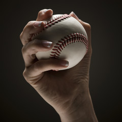 Young woman's hand holding baseball