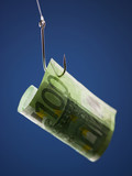 """One hundred Euros banknote on hook, against blue background"""