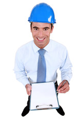 Smiling engineer holding a blank clipboard