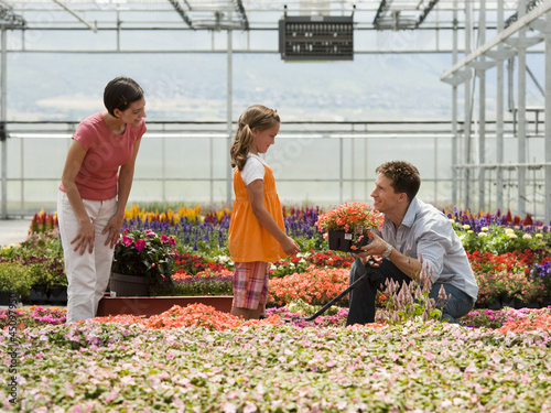 """USA, Utah, Salem, girl (8-9) with parents choosing plants in greenhouse"""