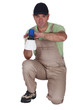 Man kneeling with paint sprayer