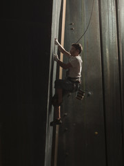 """USA, Utah, Sandy, boy climbing in indoor climbing gym, side view"""