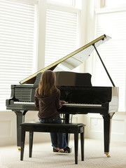 """USA, Utah, Alpine, girl (8-9) practicing piano, rear view"""