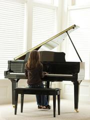 """USA, Utah, Alpine, girl (8-9) practicing piano, rear view"""