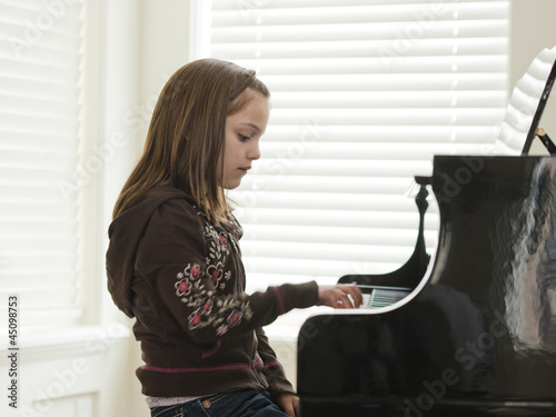 """USA, Utah, Alpine, girl (8-9) practicing piano, side view"""