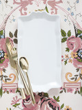 Empty plate with golden utensils on floral pattern