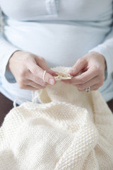 """Mid adult pregnant woman knitting, mid section """