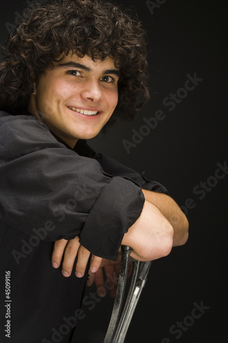 """Teenage boy (16-17) sitting backwards on chair, portrait"""