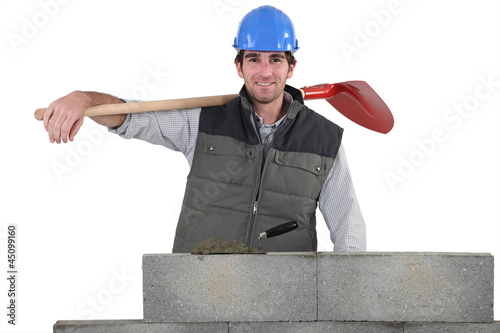 a handsome bricklayer by brickwall holding shovel