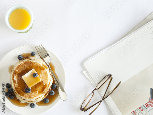 """USA, California, San Francisco, blueberry pancakes with eyeglasses and juice on table, overhead view"""