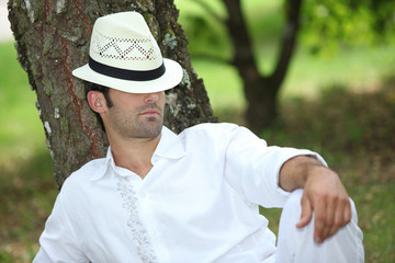 Man relaxing under tree