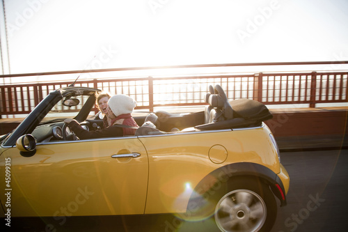 """USA, California, San Francisco, young couple sitting car with Golden Gate Bridge in background, portrait"""