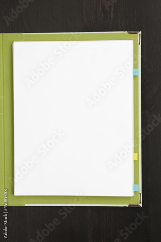"""Blank sheets of paper in green cover, studio shot"""