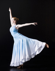 Young woman posing as professional dancer, studio shot