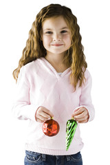 Studio portrait of girl (6-7) holding Christmas decoration