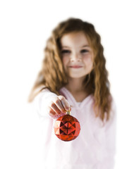 """Girl (6-7) holding Christmas decoration, focus on foreground"""