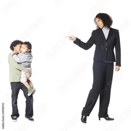 """Studio shot of mother talking to sons (18-23 months, 8-9 years)"""