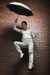 Studio shot of young woman falling holding umbrella