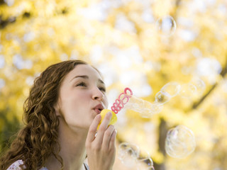 """Provo, USA, Utah, Young woman blowing bubbles in front of colorful tree, portrait"""