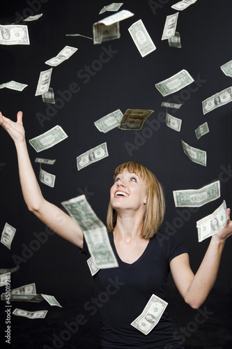 """Portrait of young woman playing with banknotes, digital enhancement"""