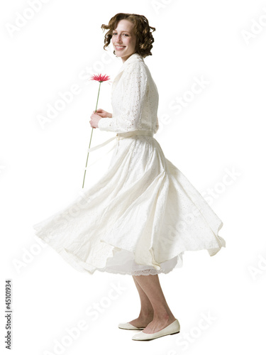 """Happy young woman dancing with gerbera flower, portrait, studio shot"""
