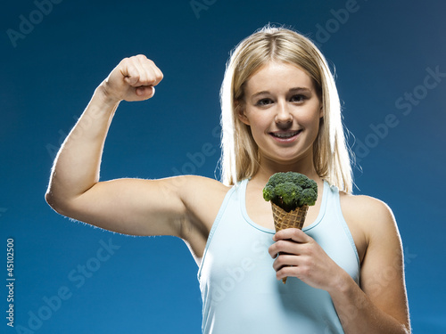 Studio portrait of young woman holding broccoli ice cream
