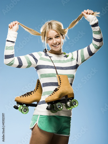 Studio portrait of young woman with roller skates