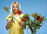 """Young woman pruning flowers, studio shot"""