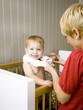 """USA, Utah, Provo, Mother dressing baby boy (18-23 months) in crib"""