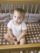 """USA, Utah, Provo, Portrait of baby boy (18-23 months) sitting in crib"""