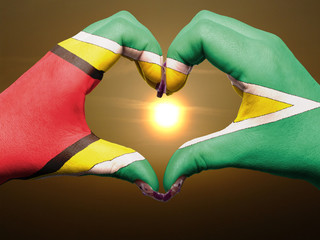 Heart and love gesture by hands colored in guyana flag during be