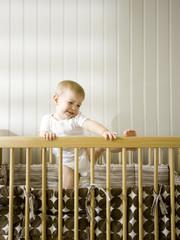 """USA, Utah, Provo, Baby boy (18-23 months) climbing in crib"""