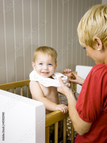 """USA, Utah, Provo, Mother dressing baby boy (18-23 months) in crib"""