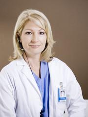 Studio portrait of female doctor using headset